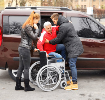 senior man carried outside the suv to his wheelchair
