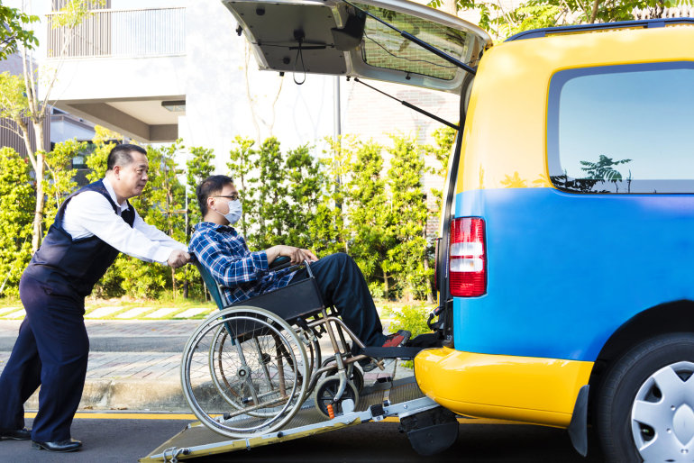 man in wheelchair carried inside the medical van